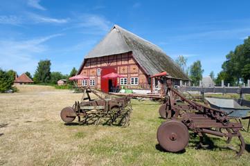 Historisches Bauernhaus mit landwirtschaftlichen Gerätschaften