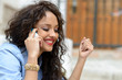 Beautiful mixed woman in urban background on the phone