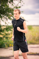 Sportive young man jogging outdoor