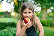 child eating a red apple with green garden as background