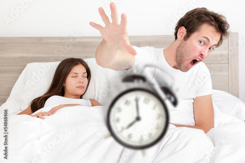 Wake up - couple waking up early throwing alarm