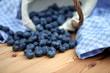 umgefallener Korb mit Heidelbeeren blaues Tuch