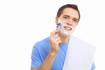 Young man at home shaving himself