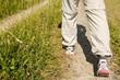 Zwei Beine wandern auf einem Weg