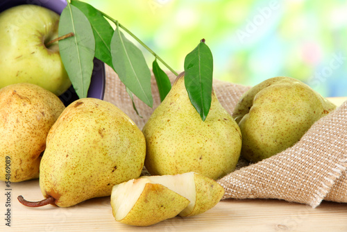 Pears in bucket on burlap on wooden table on nature background