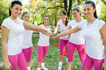 Sportswomen with hands together