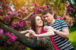 Happy loving couple are hugging blossoming apple orchard