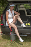 Portrait of a female tennis player & car