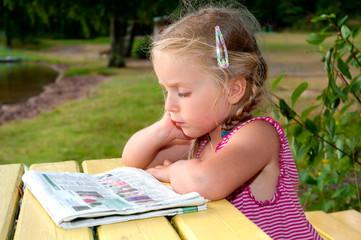 Kleines Mädchen mit Zeitung