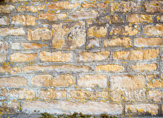 Weathered limestone wall made of the stones of different shape