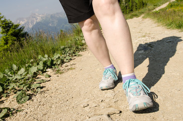 Weibliche Beine beim wandern in den Bergen