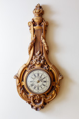 Vintage golden clock on white wall background