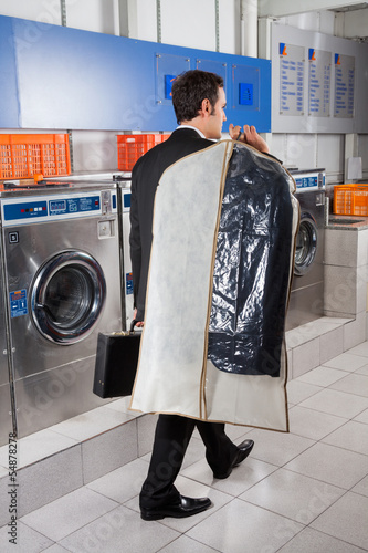 Businessman With Suitcase And Suitcover Walking In Laundry