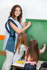 Teacher And Children Writing On Chalkboard In Classroom