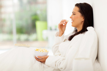 young woman sitting on bed eating popcorn and watching tv