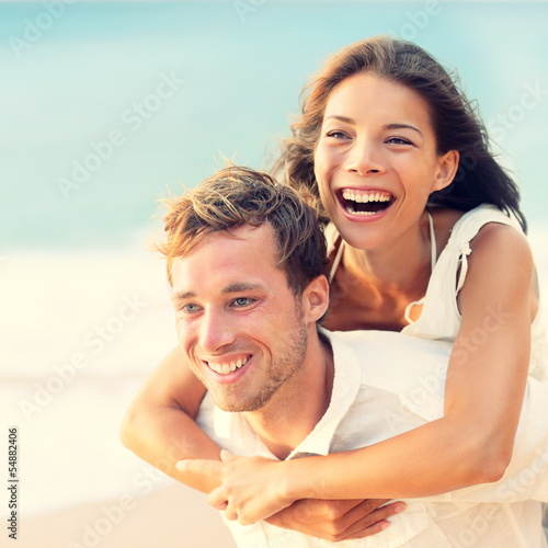 Love - Happy couple on beach having fun piggyback