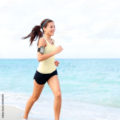 Running woman jogging on beach listening to music