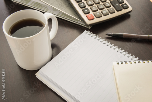 Coffee cup, Document file , pen , Calculator , notepad  on woode