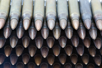 A stack of 5.56mm rifle cartridges. Shot from a high angle.