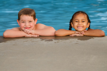 Portrait of Caucasian boy and mixed race girl in pool