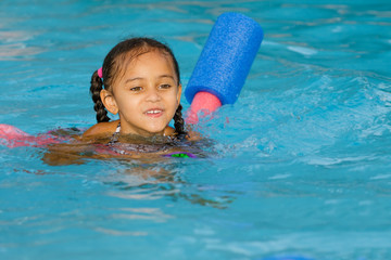 Pretty mixed race child swimming in pool during summer