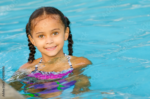 Portrait of happy pretty mixed race child by side of pool