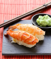 portion of sushi with shrimp on a stone plate
