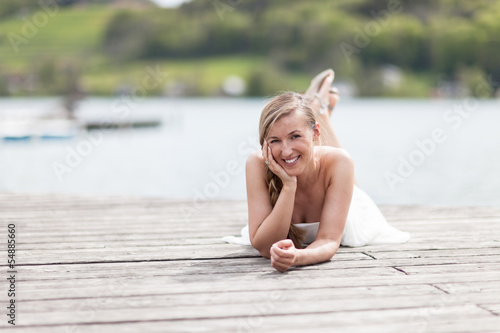 Joyful woman relaxing on a wooden deck at the sea
