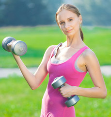 Woman exercising with dumbbell at city park
