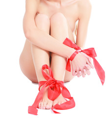 Female legs and hands with red ribbons
