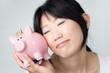 Glückliche Frau mit Sparschwein