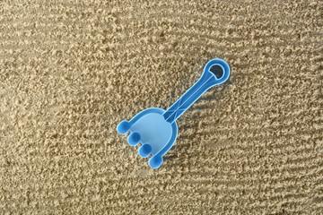 Rastrillo azul de juguete en la arena