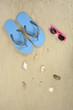 Chanclas azules, gafas y conchas en la arena