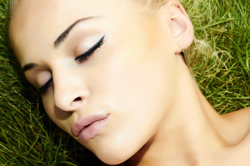 Beautiful blond girl on green grass. beauty woman. sleep