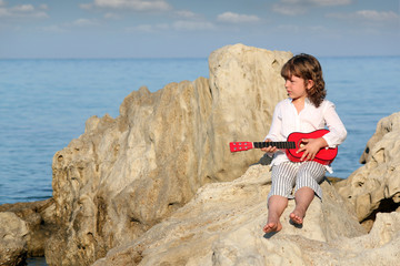 little girl with guitar sitting on rock