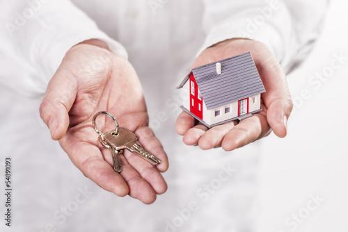 Hände mit Modellhaus und Schlüssel