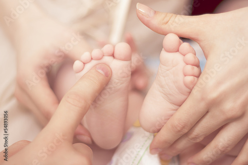 close up of baby's heels and parent's hands