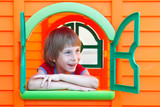 Cute little boy playing in toy house on playground