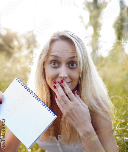 Cute blonde girl holding a white notebook for your text