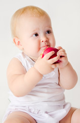 baby girl biting an apple