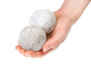 Woman's hand holding round halite salt crystals