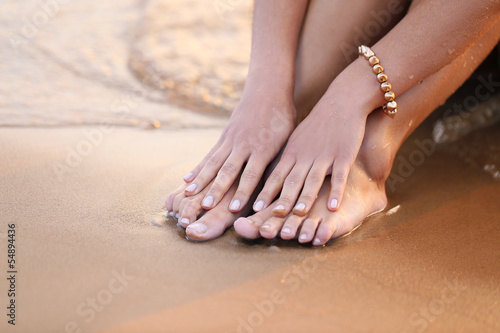 Feet and hands on a beach