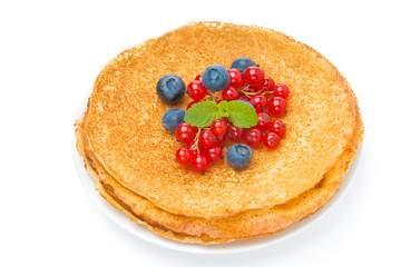 stack of crepes with red currants and blueberries on a plate
