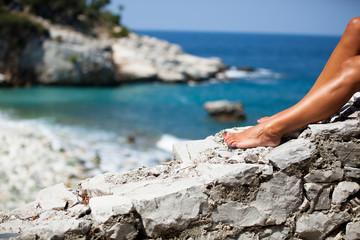 Frauenfüsse auf Natursteinmauer am Meer
