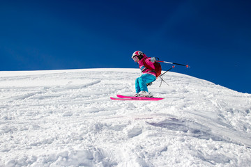 Little girl skier flies over the slope