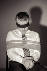 Kidnapped businessman. Black and white image of Tied up man in s
