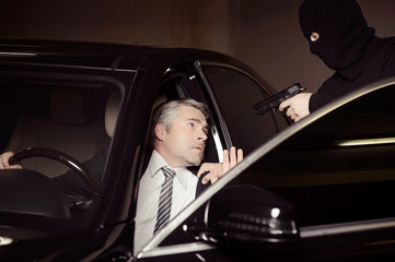 Attacking a businessman. Men in black balaclava holding gun and