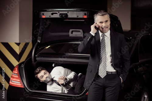 Kidnapped man. Tied up businessman lying in the car trunk and lo