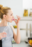 Young woman eating pill in kitchen