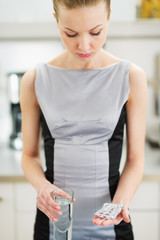 Frustrated young woman looking on pills